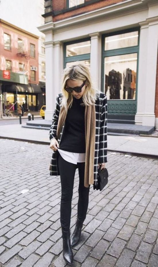 a layered winter look with black skinnies, a white shirt, a black jumper, a short printed coat, black boots, a black bag