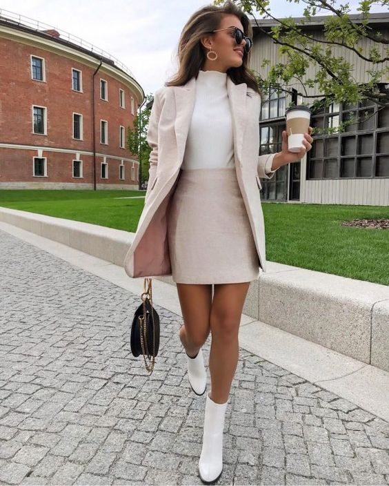 a light pink suit with a mini skirt and an oversized blazer, a white turtleneck, white boots, a black bag