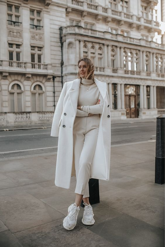 a lovely neutral monochromatic look with a turtleneck, cropped pants, trainers, a coat and a necklace is comfy