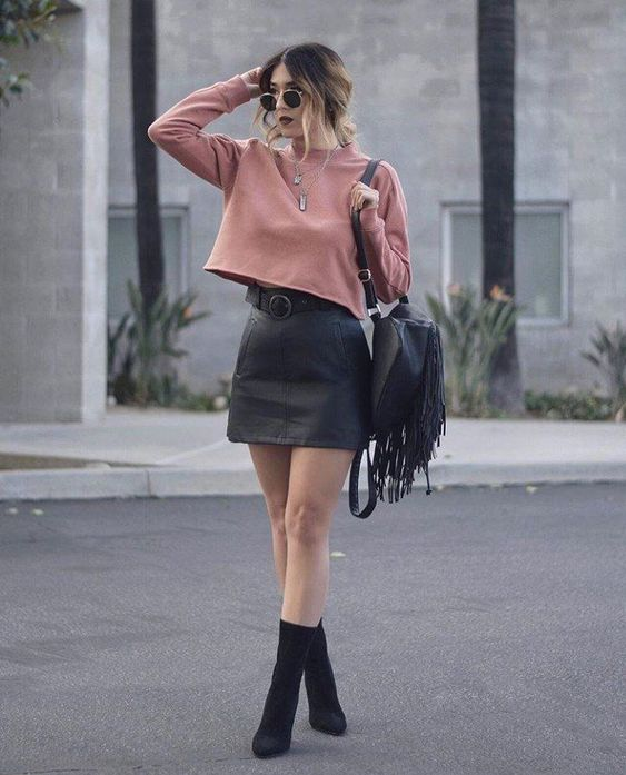 a mauve sweatshirt, a black leather mini, black sock boots and a black fringed bag