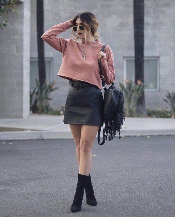 a mauve sweatshirt, a black leather mini, black sock boots and a black fringed bag
