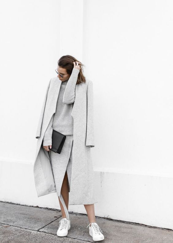 a minimal outfit with a sweater, wrap midi skirt, a midi coat, white sneakers and a black clutch
