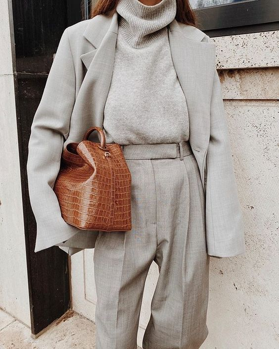 a minimalist look with grey trousers, a turtleneck, a blazer and a brown crocodile leather bag for an accent