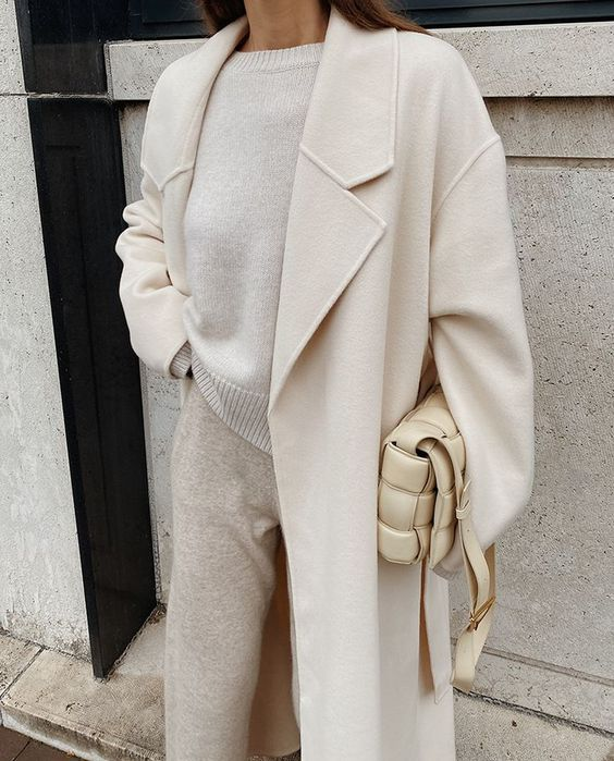 a monochromatic neutral look with a jumper, joggers, a midi coat and a woven bag