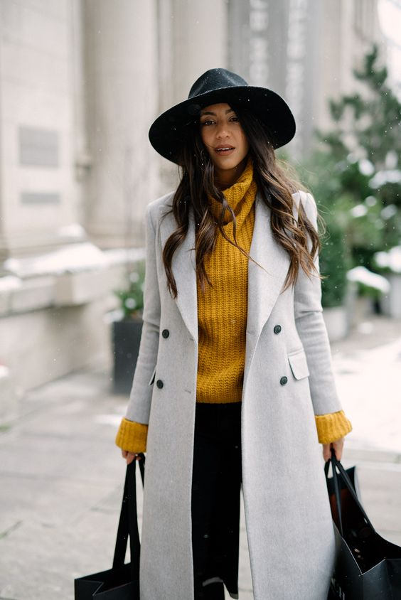 a mustard sweater, black jeans, a dove grey coat, a black hat for a trendy winter look