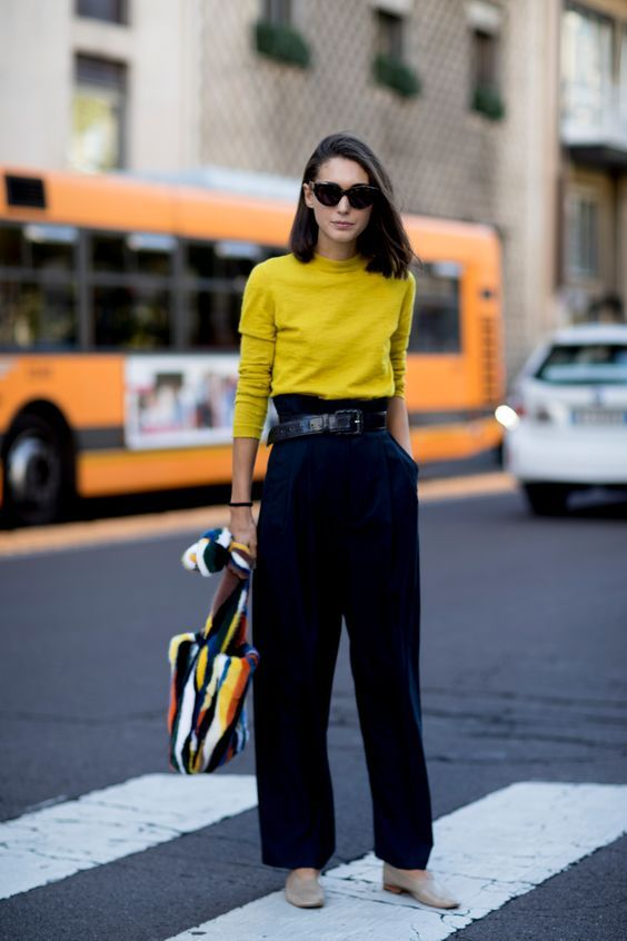 a mustard top, black high waisted pants, neutral shoes, a colorful striped bag for spring