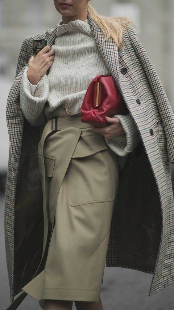 a neutral chunky sweater, a camel leather wrap skirt, a plad coat and a red bag for a cold day