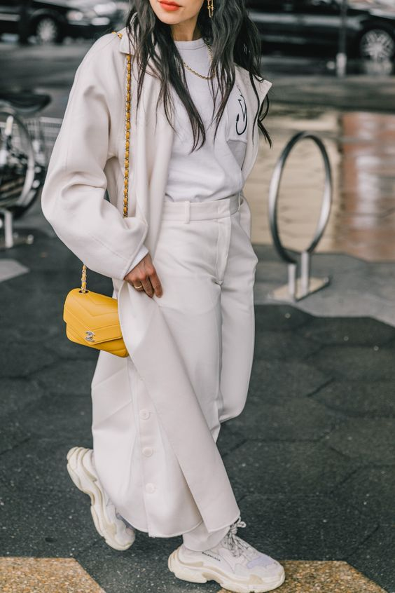 a neutral look with a tee, white jeans, trainers, a midi coat, a honey yellow bag for spring