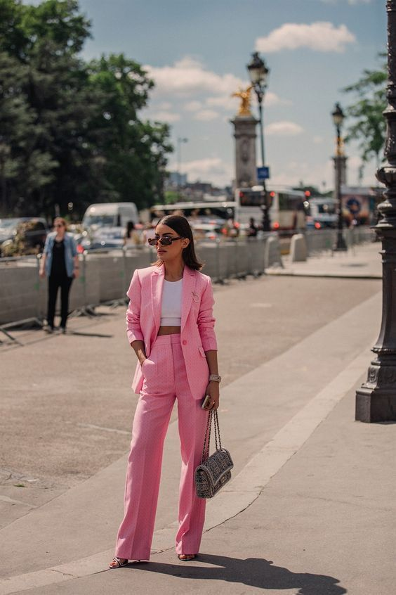 a pink pantsuit with an oversized blazer, a white crop top, heels and a tweed bag for work