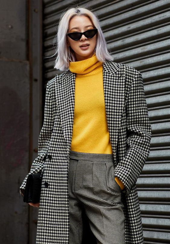 a printed black and white look with pants and a coat spruced up with a yellow turtleneck and a black clutch
