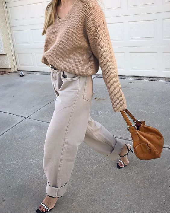 a relaxed and chic look with a tan ribbed V-neck sweater, neutral barrel jeans, embellished shoes and a camel bag