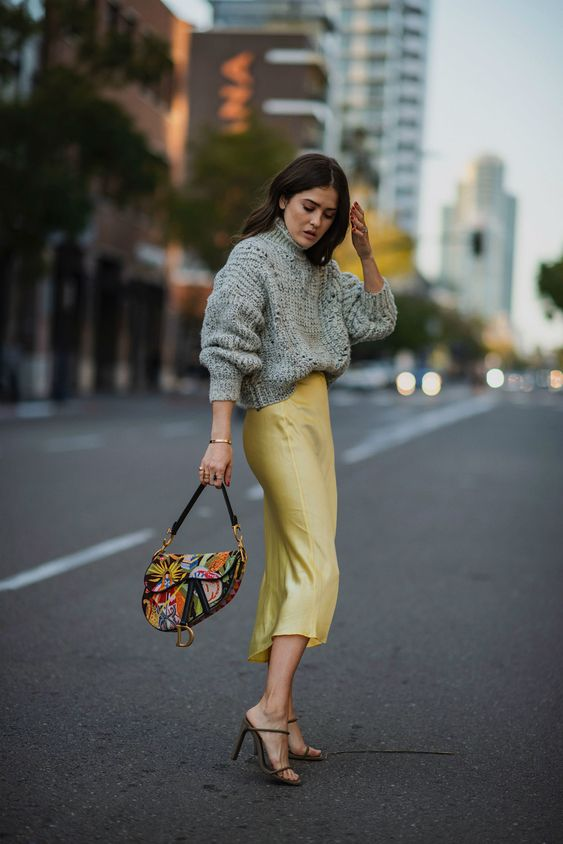 a satin midi skirt or dress, an oversized grey turtleneck sweater, strappy heels and a bold bag