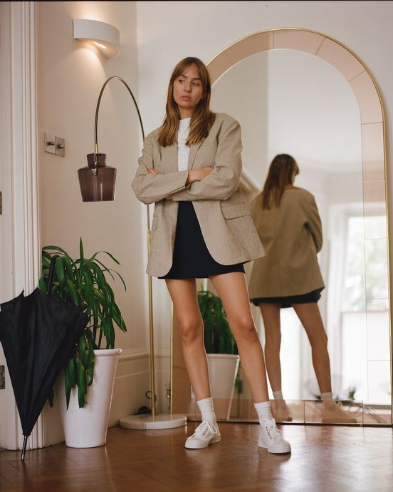 a simple look with a white tee and sneakers, a black mini, a tan oversized blazer for spring or summer