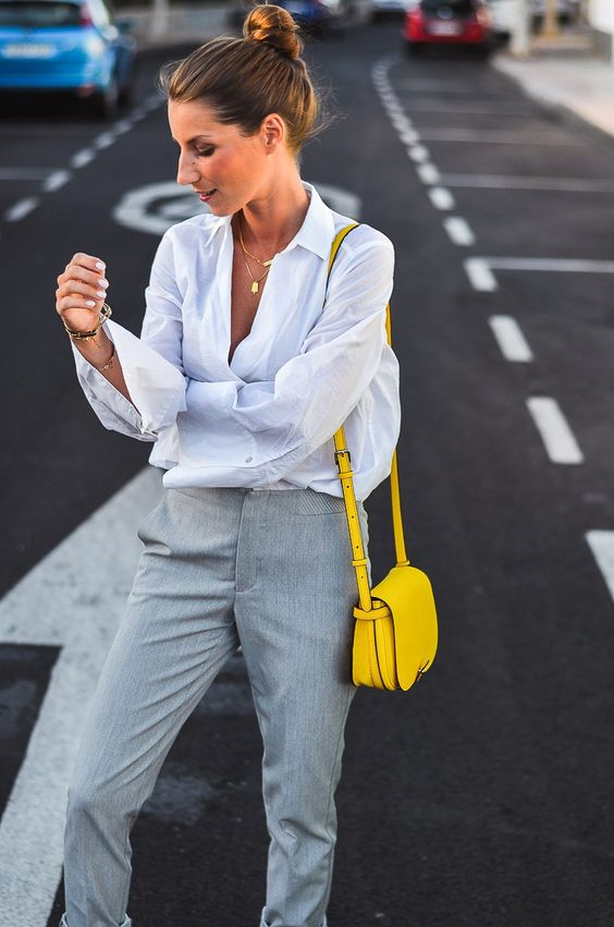 a simple work outfit with a white shirt, grey pants and a lemon yellow crossbody bag that makes a statement