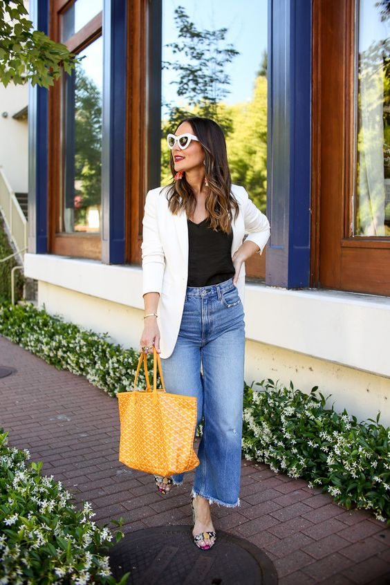a spring to summer look with a black top, blue straight jeans, a white oversized blazer, floral shoes and a yellow tote