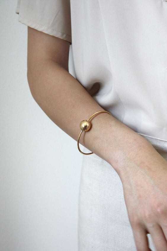 a statement gold bracelet with a sphere is a cool idea to look very actual and chic right now