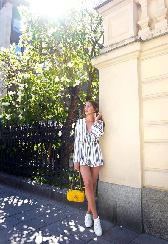 a striped jumpsuit with long sleeves, white sneakers and a yellow bag for a simple summer look