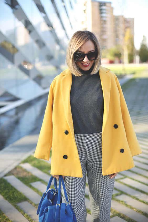 a stylish look with a grey turtleneck, grey gingham pants, a yellow jacket and a bold blue bag