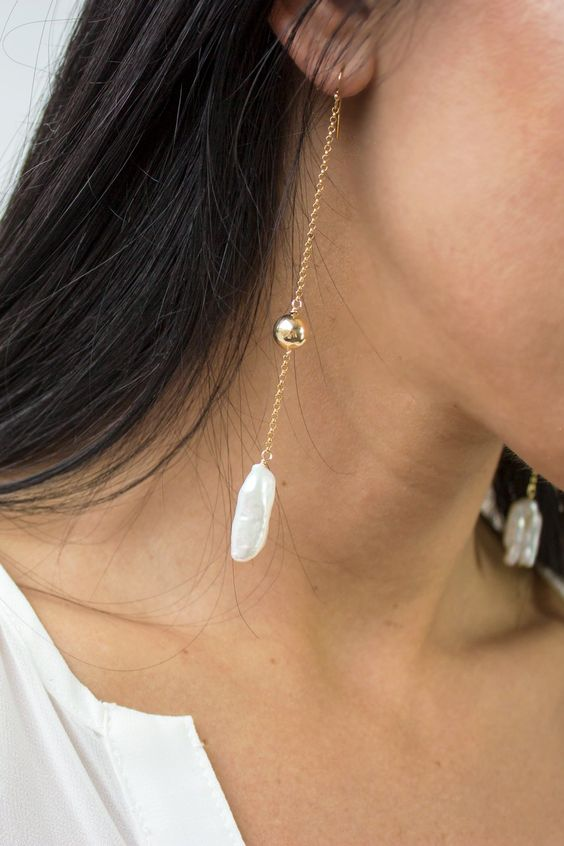 a super trendy earring of a gold chain with a ball and a baroque pearl features two trends in one