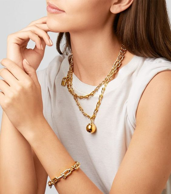 a super trendy gold chain necklace with a sphere and a lock is an edgy solution to accessorize your look
