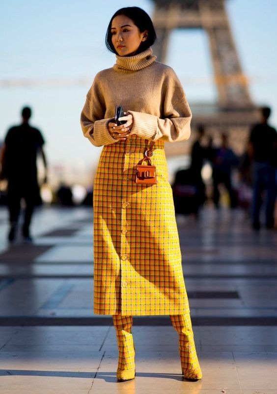 a tan oversized turtleneck sweater, a yellow button up midi skirt and matching boots and a mini bag