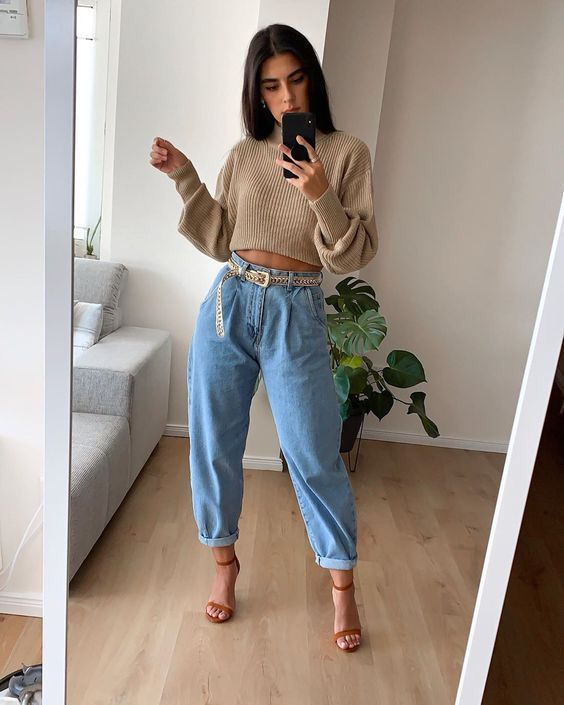 a tan ribbed and cropped sweater, blue barrel jeans, rust heels and a gold belt for a sexy look