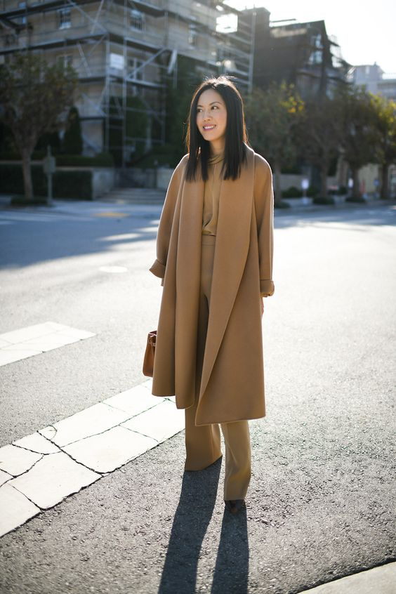 a total beige outfit with a blouse, trousers, heels, a midi coat and a camel bag for work