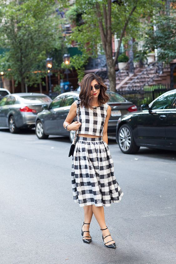 a two piece black and white check look with a sleeveless crop top and a pleated midi, black strappy shoes and a black bag