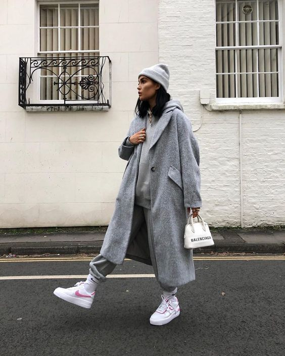 a very relaxed total grey look with a tracksuit, a midi coat, a beanie, white trainers and a white bag