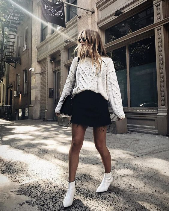 a white boho jumper, a black denim mini skirt, white booties, a black bag for a cold spring day