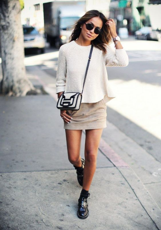 a white jumper, a tan mini, black shoes and socks, a graphic black and white bag
