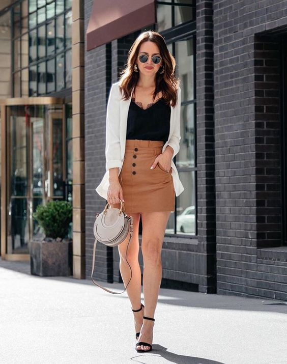 a white lingerie top, a brown high waisted mini skirt with pockets, black heels,a white blazer and a round bag