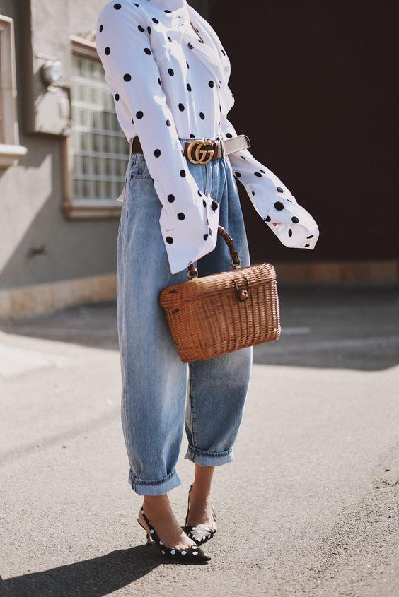 a white polka dot shirt, light blue barrel jeans, black polka dot shoes and a basket instead of a bag