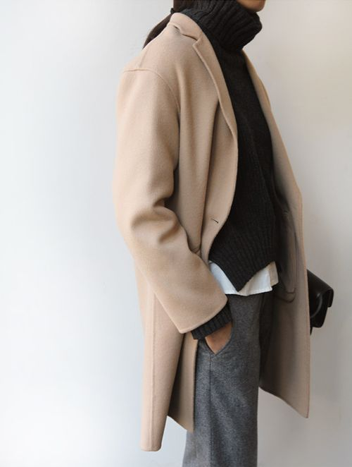 a white shirt, a black turtleneck sweater, grey woolen pats, a camel short coat and a bag