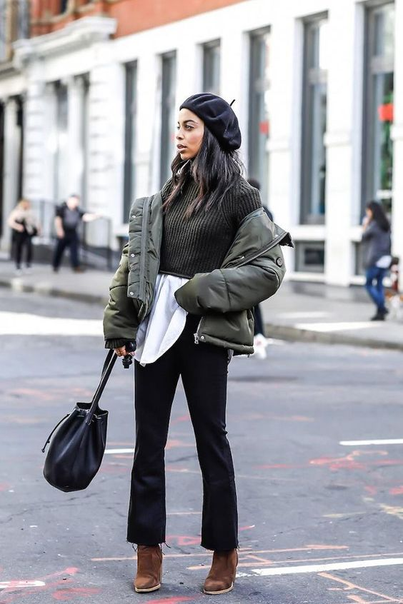 a white shirt, a green cropped sweater, black pants, brown boots, a green leather puff jacket, a black bag