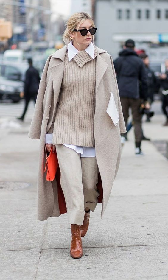 a white shirt, a neutral oversized sweater, matching pants and a coat, brown boots and an orange clutch
