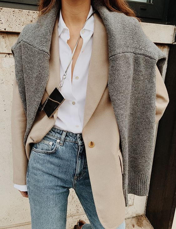 a white shirt, a tan blazer, blue jeans, a grey sweater over it and a tiny black bag for winter