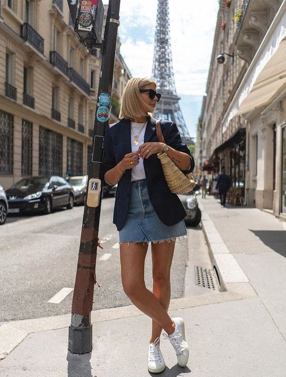 a white tee, a black blazer, a blue denim mini skirt, white sneakers and a straw bag plus layered necklaces