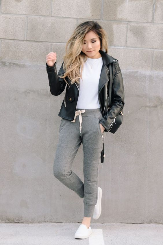 a white tee, a black leather jacket, grey joggers, white slipons and a black bag for transition