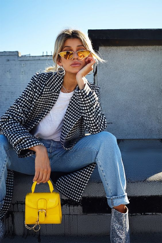 a white tee, blue jeans, silver booties, a black and white printed coat, a sunny yellow mini bag with chain