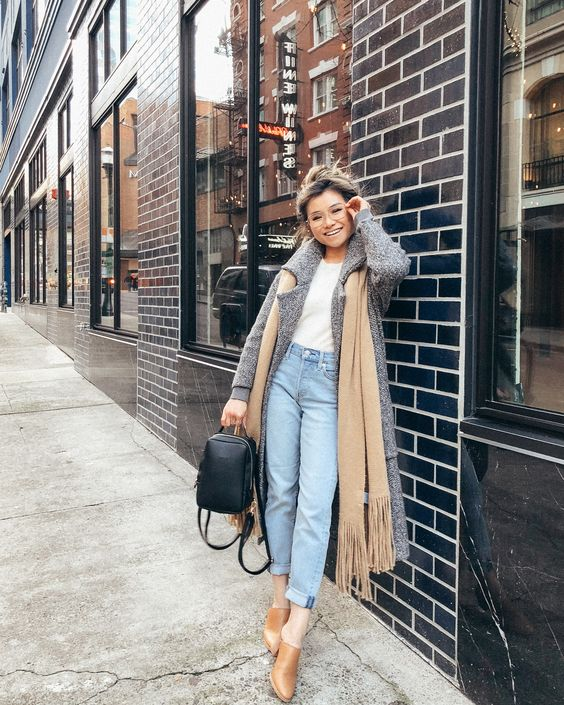 a white tee, light blue jeans, cognac shoes, a grey coa, a tan scarf and a black backpack