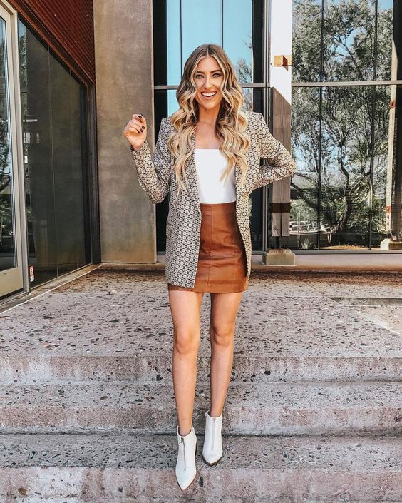 a white top, a printed oversized blazer, a brown leather mini skirt, white boots for a cool look