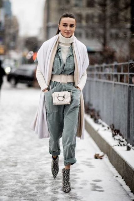 a white turtleneck, a green jumpsuit, a belt, snakeskin boots, a white bag and a white coverup