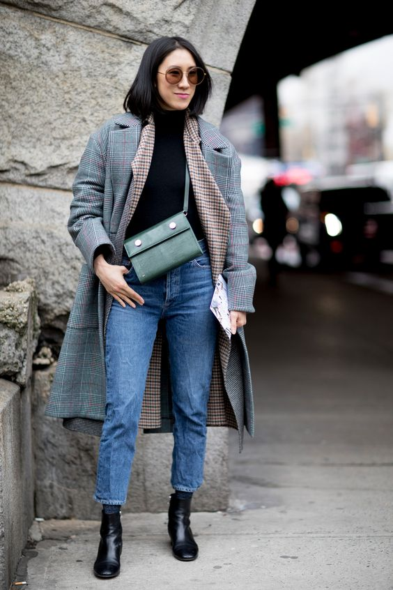 a winter outfit with a black turtleneck, blue jeans, a printed blazer and a grey plaid coat plus black boots