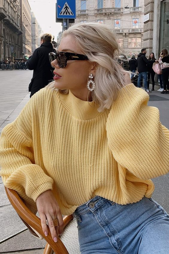 a yellow chunky knit sweater, blue jeans, statement earrings are all you need for a bold winter look