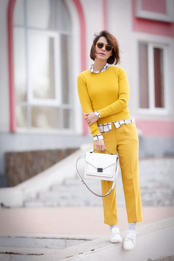 a yellow look with a jumper and pants, a windowpane print shirt, white sneakers and a white bag
