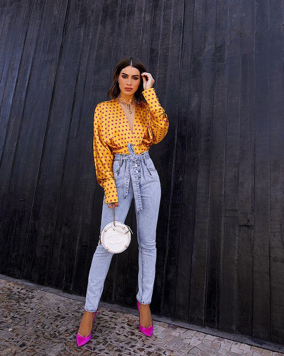 a yellow polka dot blouse, blue high waisted jeans, hot pink shoes and a white round bag