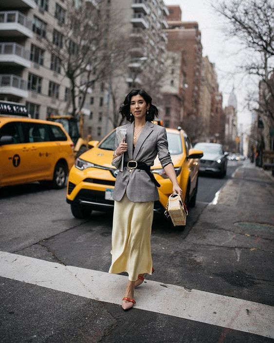 a yellow satin slip dress, a grey blazer over it, a black belt, a yellow bag and blush shoes with orange belts