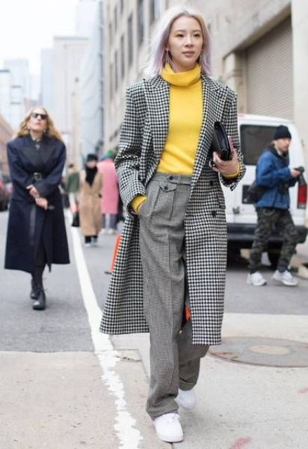 a yellow turtleneck, grey trousers, white sneakers and a black and white printed coat