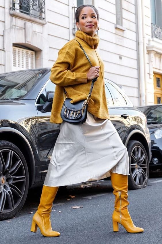 a yellow turtleneck sweater and boots, a neutral midi skirt, a black embellished bag